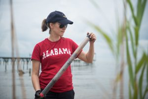 student wearing an Alabama t-shirt standing by a body of water