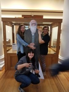 students posing with statue of Charles Darwin